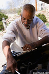 African American senior man with short gray hair and a goatee reading a car repair manual and working under the hood of his car. The man is older, with gray hair and a gray beard. The amateur auto mechanic is wearing a white shirt.